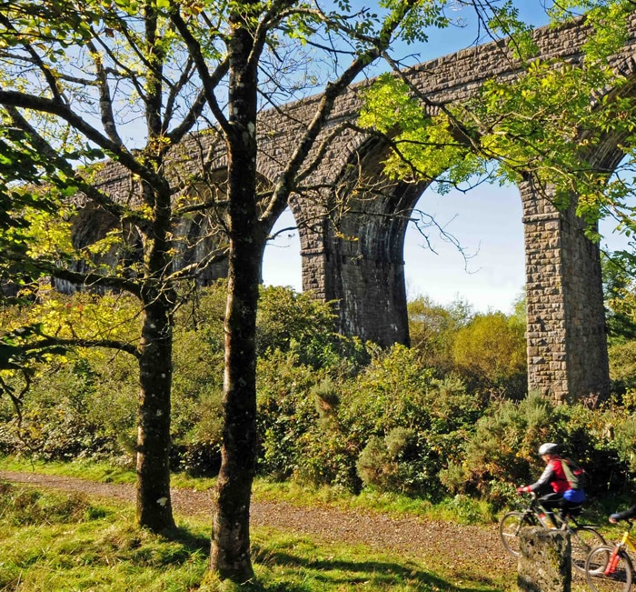 Photo of cyclists on a trail under a viaduct on the Granite Way