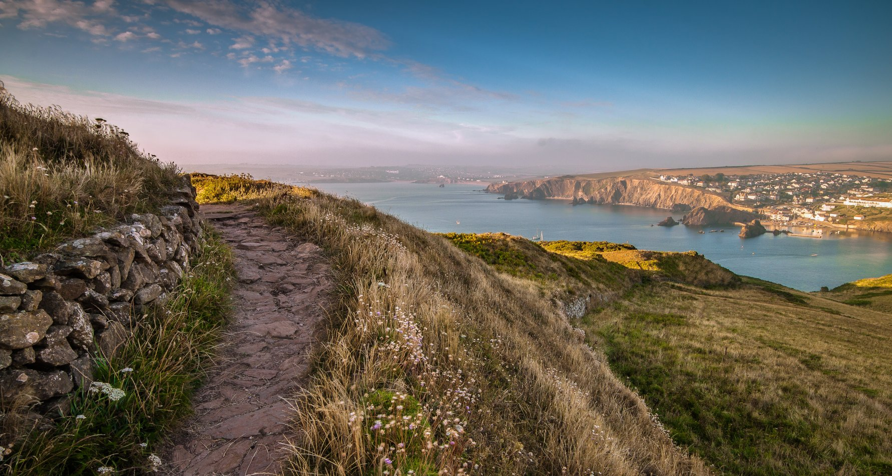 Landscape photo from the south west coast path at Bolt Tail across fields and the sea to coastal cliffs and Hope Cove