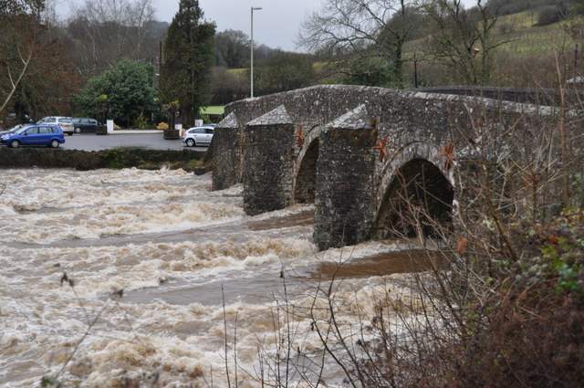 Photo of flood water rushing beneath an old stone bridge at Bickleigh