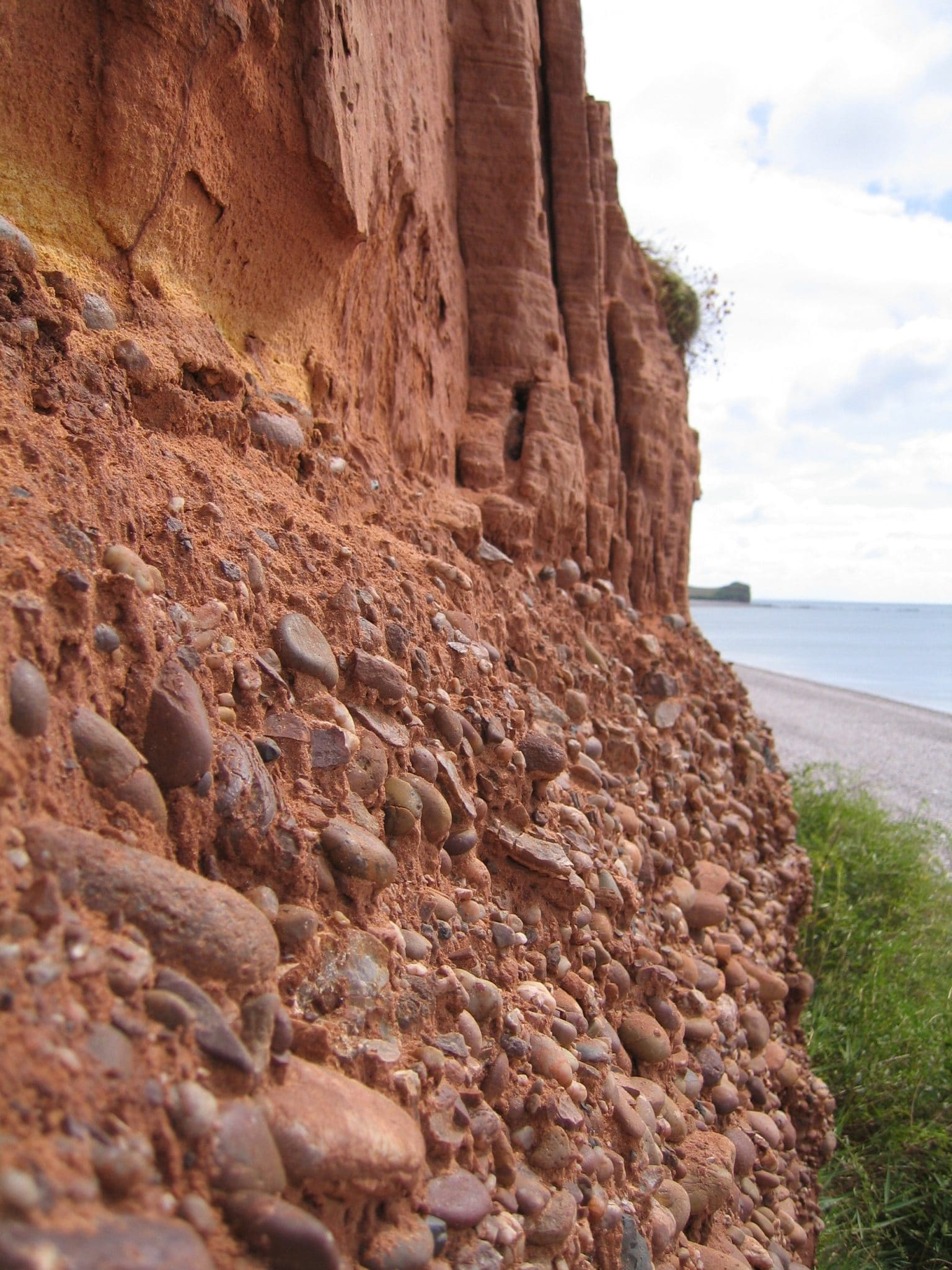 Photo of red cliffs and pebble bed layer above Budleigh Salterton Beach