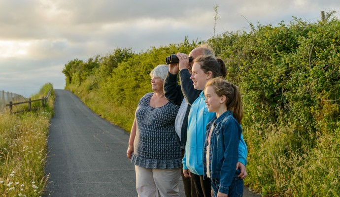 Photo of walkers on the Exe Estuary Trail looking through binoculars