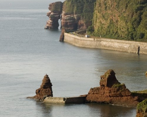 Photo looking along the coast over the sea and red rocks to Parsons tunnel at Dawlish