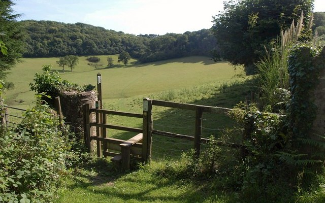 Photo of a stile in front of fields and woodland