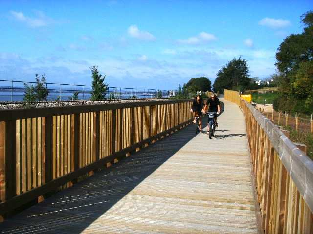 Photo of cyclists crossing a wooden bridge on the Exe Estuary Trail
