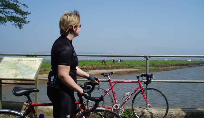 Photo of a cyclist looking out over the Exe Estuary at Turf Locks
