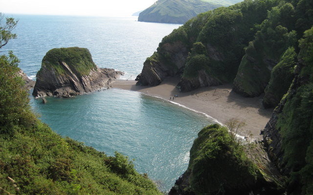 Photo looking down on sea and beach with rocky cliffs behind