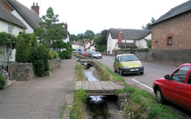 Photo of a street through Otterton lined with thatched cottages and a small stream