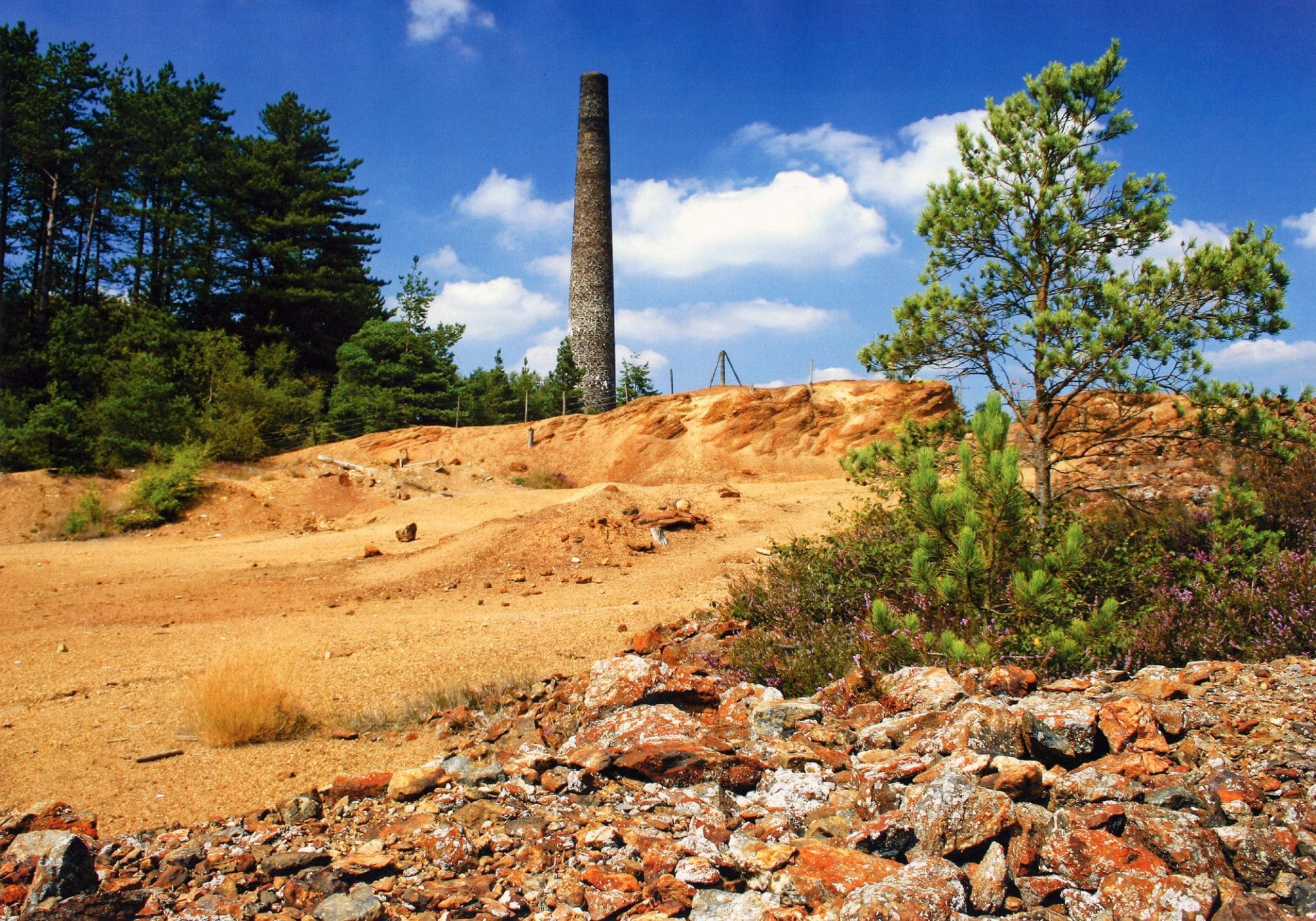 Photo of an arsenic mine tower with waste ground in front