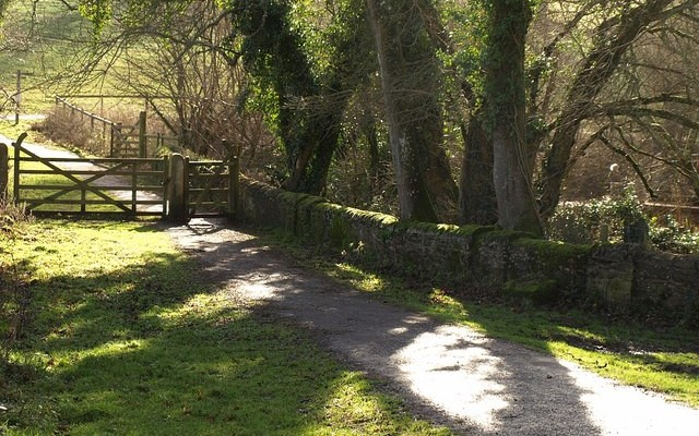 Photo of a quiet lane alongside a stone wall to a footpath gate