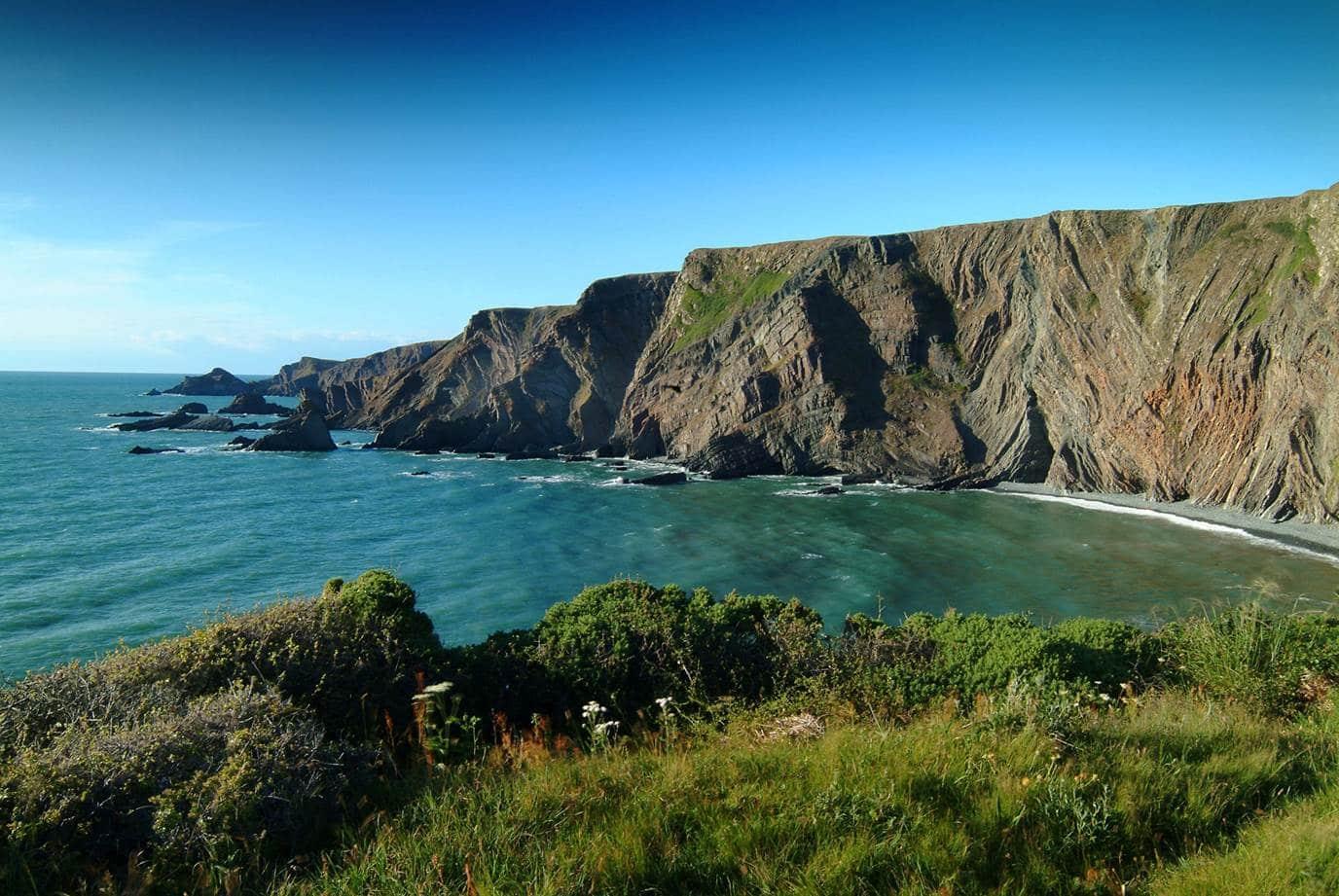 Photo of the Hartland Peninsula showing coastal cliffs and sea