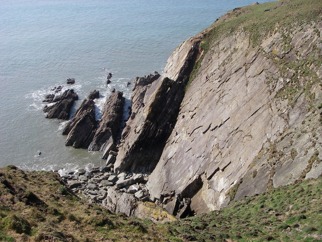 Photo looking down over rocky coastal cliffs towards the sea at Baggy Point