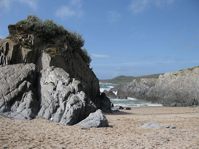 Photo looking across sand and through rocks to the sea at Barricane beach
