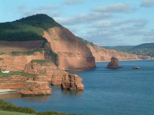 Photo looking across Ladram Bay in East DEvon with red cliffs and sandstone stacks