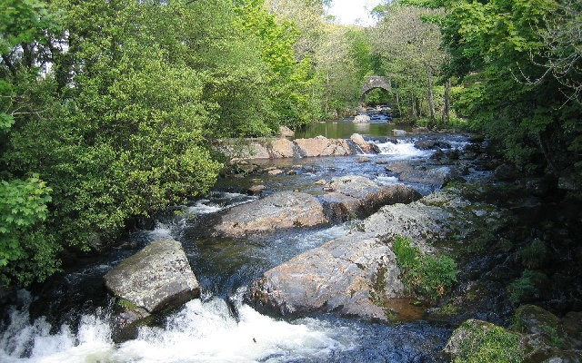 Photo of the River Erme running over rocks with a bridge in the background