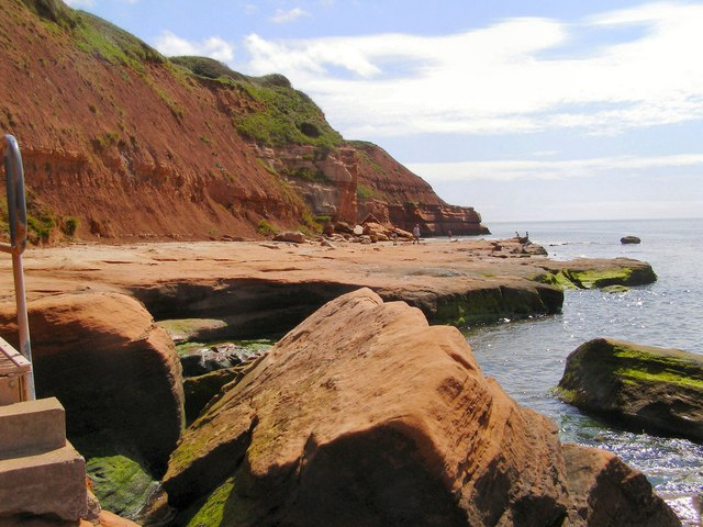 Photo of the red sandstone shore and sea with cliffs behind near Orcombe Point in Exmouth
