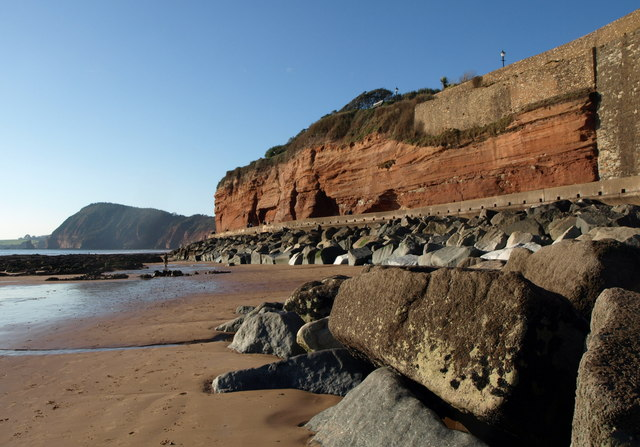 Photo of the red cliffs on Sidmouth seafront with High Peak hill in the background