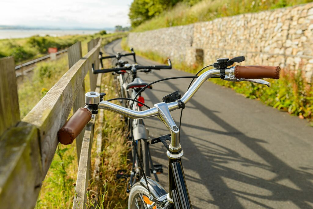 Photo of a line of bicycles standing against a fence on the Exe Estuary Trail