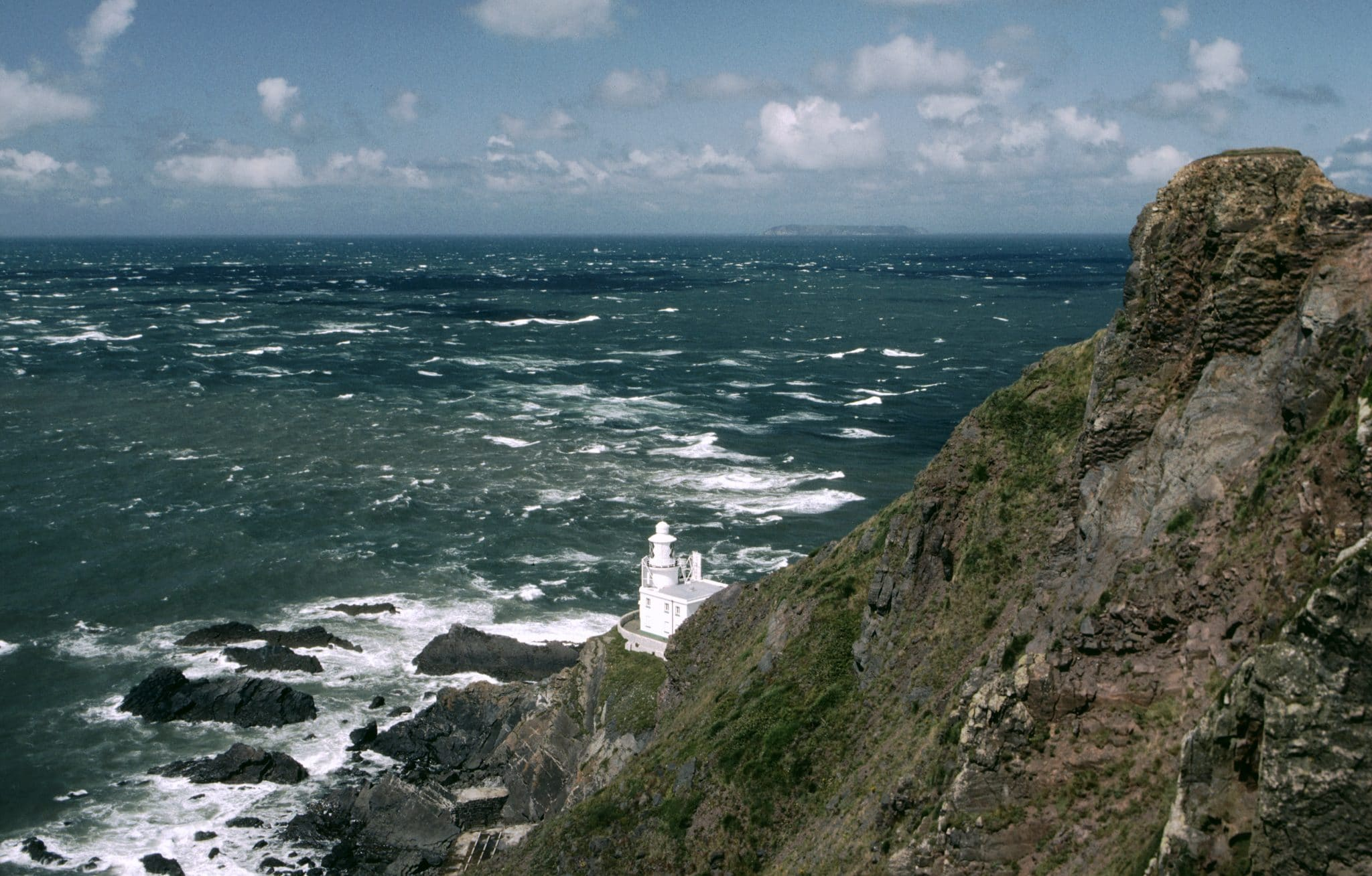 Photo of the light house at Hartland point in north Devon, looking down the cliffs to the lighthouse and out over a rough sea towards Lundy