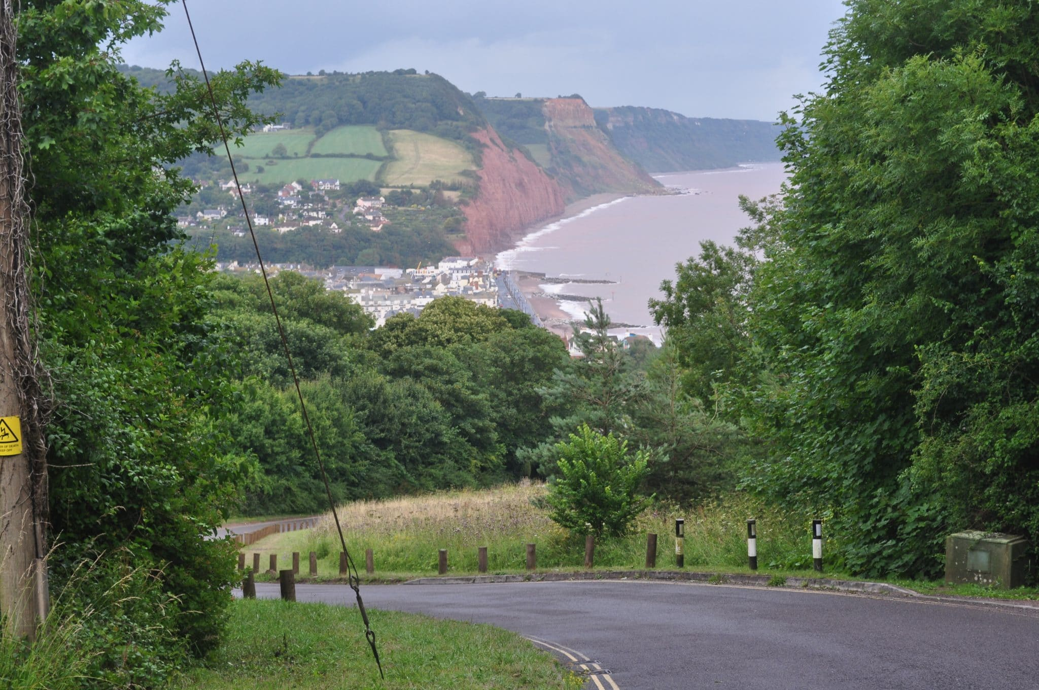 Photo looking down into Sidmouth from Peak Hill with the town in the bottom of the valley and the sea and red cliffs in the background