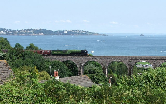 Photo of Broadsands viaduct with a train crossing it and the sea and coastline in the background