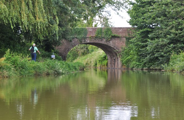 Photo of the Grand Western canal with a walker on the towpath and Tidcombe Bridge over the canal