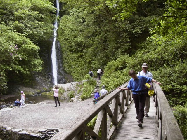 Photo of a bridge and waterfall at White Lady Waterfall in Lydford Gorge