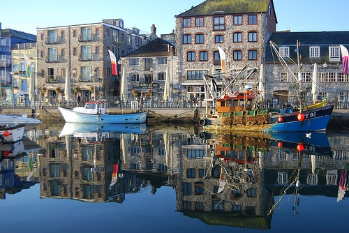 Photo of boats in a marina in front of buildings at Plymouth Barbican