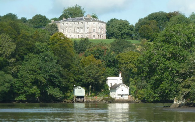 Photo looking across the river Dart to the boathouse at Sharpham House with the main house on the hill behind