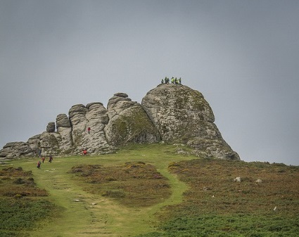 Photo of Haytor on Dartmoor with walkers climbing up to it and standing on the top