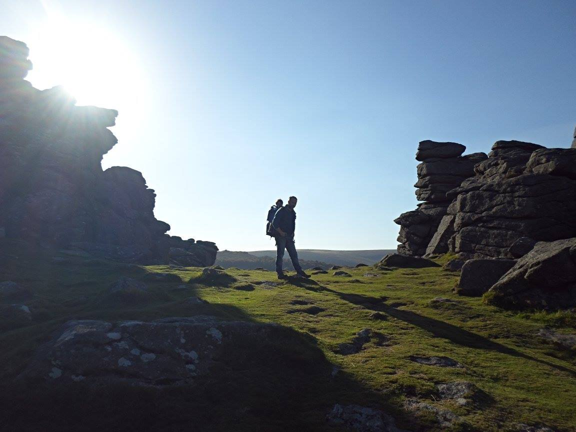 Photo of a man and baby ina back pack between rocks at Hound Tor