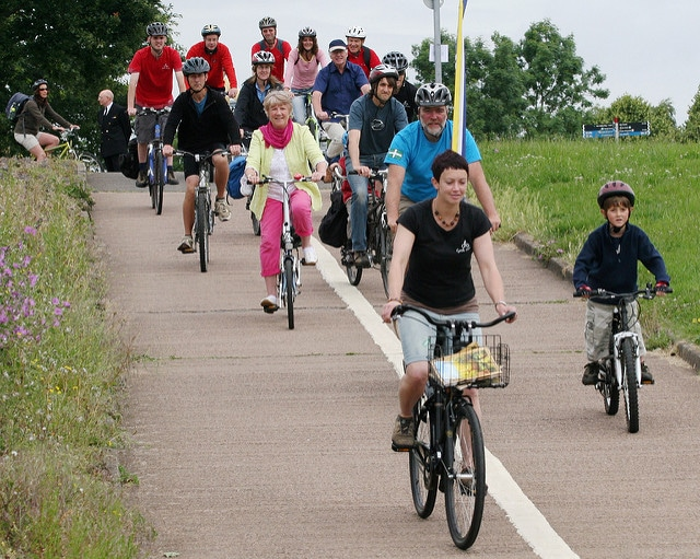 Photo of a group of adults and children cycling along a cycle path