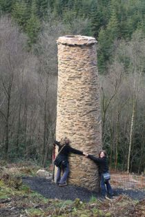 Photo of people holding hands around an old mining chimney on Exmoor