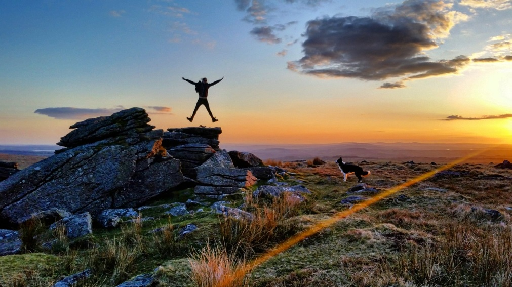 Photo of a walker jumping for joy on rocks at Leeden Tor, Dartmoor at sunset while a dog watches