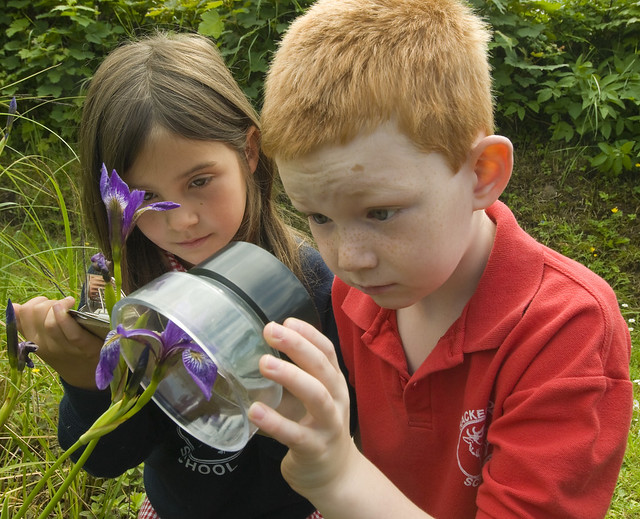 Photo of two children looking at a flower through a magnifying lens