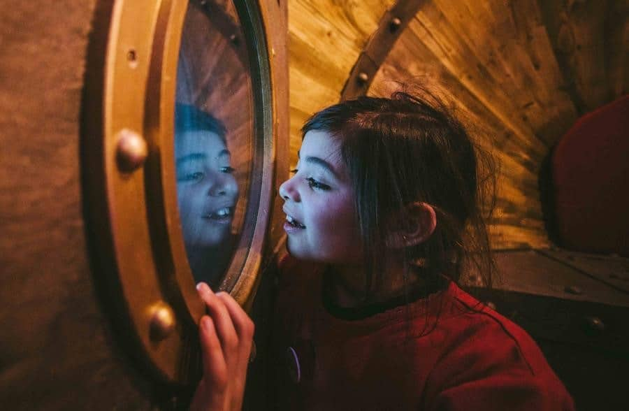 Photo of a girl looking through a portal window in the Seaton Jurassic time machine